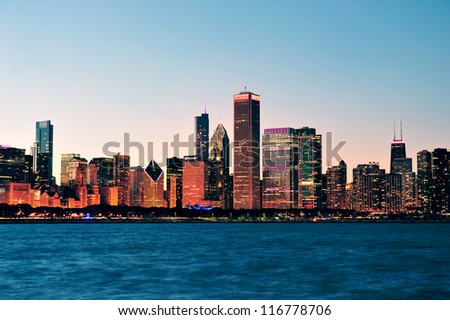 Chicago city downtown urban skyline at dusk with skyscrapers over Lake Michigan with clear blue sky.