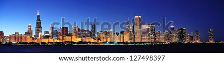Stock Photo Chicago city downtown urban skyline panorama at dusk with skyscrapers over Lake Michigan with clear blue sky.