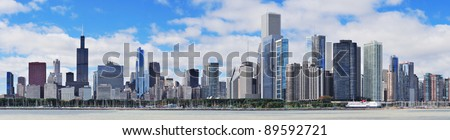 Chicago city urban skyline panorama with skyscrapers over Lake Michigan with cloudy blue sky.