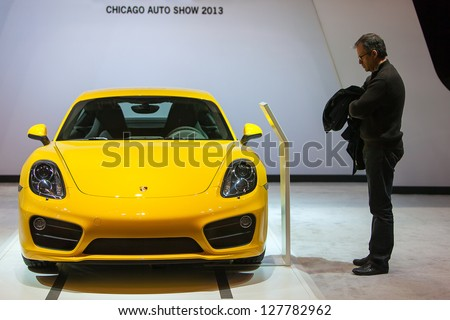 CHICAGO - FEBRUARY 8 : A visitor looks at the new 2014 Porsche Cayman at the Chicago Auto Show media preview February 8, 2013 in Chicago, Illinois.