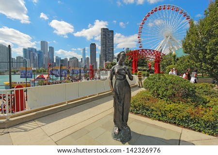 CHICAGO, ILLINOIS - SEPTEMBER 4: Statue, tourists and rides at the Navy Pier in Chicago, Illinois on September 4, 2011. The Pier is a popular destination with many attractions on Lake Michigan.