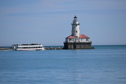 Chicago, Illinois, USA - April 1 2017: The view of Lake Michigan on the shore of Ohio Street Beach in Chicago next to Navy Pier. The Chicago Harbor Lighthouse and boat with many passengers.