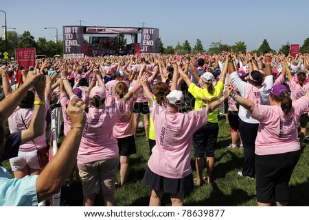 CHICAGO - JUNE 5: Participants raising their hands at the final ceremony festivities at the Avon Walk for Breast Cancer outside Soldier Field on June 5, 2011 in Chicago, IL.
