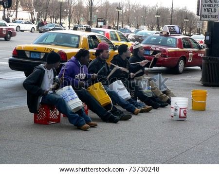 """CHICAGO - MARCH 19: """"Bucket boys"""" entertain passers-by with their drumming on Michigan Avenue in Chicago on March 19, 2011."""