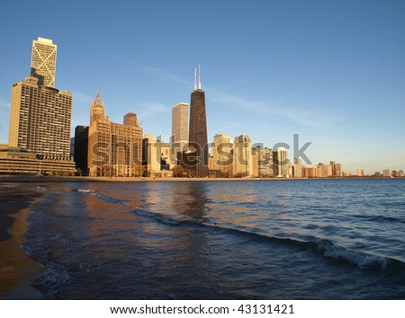 Chicago sandy beach front and towers in warm morning sunlight.