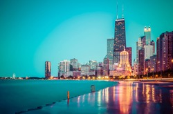 Chicago skyline at sunset with cloudy sky and reflection in water.
