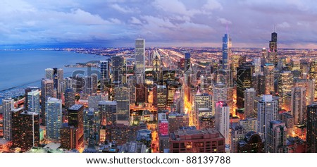 Chicago skyline panorama aerial view with skyscrapers over Lake Michigan with cloudy  sky at dusk.