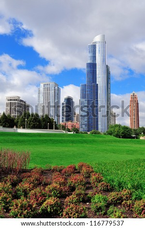 Chicago skyline with trees and law with cloudy blue sky.