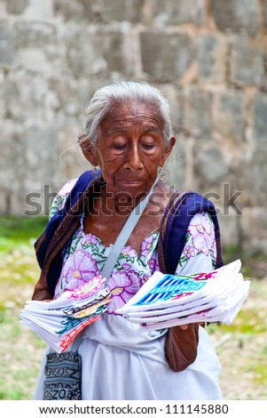 CHICHEN ITZA, MEXICO - AUGUST 15: Elderly woman selling traditional mayan handkerchiefs and napkin in Chichen Itza site on August 15, 2012 in Yucatan, Mayan Riviera, Mexico