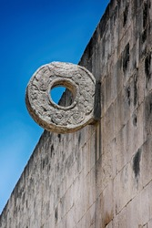 Chichen Itza - the wall of the Great Ball Court, high walls are rings carved by intertwined feathered snakes, beautiful blue sky.