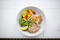Chicken and buckwheat dish with green beans, broad beans, tomato, and pepper slices from above. Nutritious dish with vegetables and meat. Healthy balanced diet