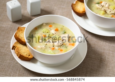 Chicken and potato chowder soup with green bell pepper and carrot in bowls with toasted bread slices on the side, photographed with natural light (Selective Focus, Focus one third into the first soup)