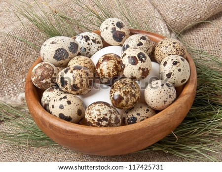 chicken and quail eggs in wooden bowl