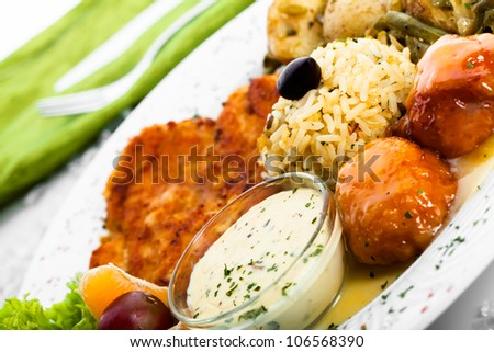 Chicken and rice being served with pumpkin cakes and potatoes.