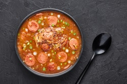Chicken and Sausage Gumbo soup in black bowl on dark slate backdrop. Gumbo is louisiana cajun cuisine soup with roux. American USA Food. Traditional ethnic meal