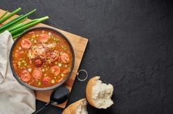 Chicken and Sausage Gumbo soup in black bowl on dark slate backdrop. Gumbo is louisiana cajun cuisine soup with roux. American USA Food. Traditional ethnic meal. Copy space