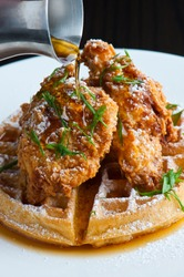 Chicken and waffles. Crispy homemade fried chicken on top of home buttermilk waffles topped with butter and maple syrup. Classic American Diner Style Breakfast or Brunch menu item.