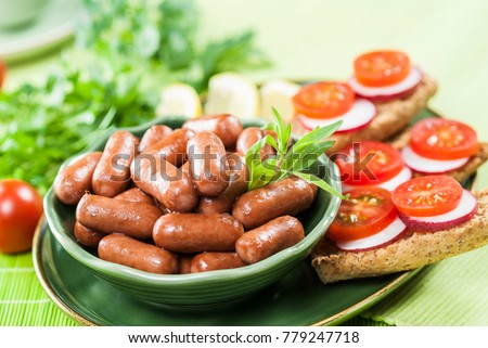 Chicken & Beef cocktail sausage with cherry tomato radish and lemon with green herb with toast bread on green red and bamboo background  with white and green plate