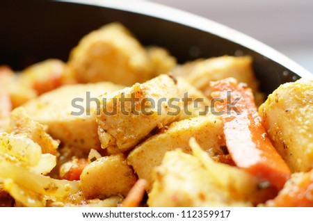 Chicken being fried in pan with onions and carrot