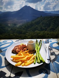 Chicken breast with French fries and boiled asparagus on white plate for breakfast with volcano view.
