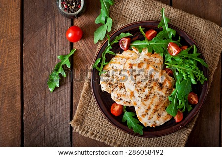 Chicken breast with fresh salad - arugula and tomato