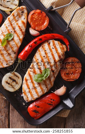 Chicken breast with tomatoes and peppers on the grill pan closeup.vertical view from above