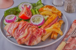 Chicken breast wrapped in bacon with salad and chips.