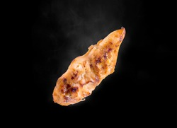 chicken breat grill with smoke on the black background studio