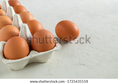 Chicken brown fresh raw eggs in an egg container. Ingredients for cooking. Healthy eating is a concept. Horizontal orientation, selective focus.