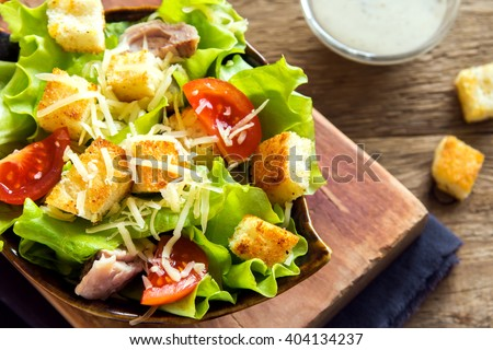 Chicken caesar salad with cheese, tomatoes and croutons close up #404134237