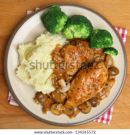 Chicken chasseur dinner served with mashed potato and broccoli.