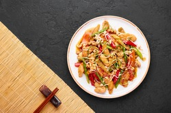 Chicken Chop Suey in white plate at black slate background. Chop Suey is American Chinese cuisine dish with different stir fried vegetables, chicken meat, sauces. Copy space. Top view. American food.