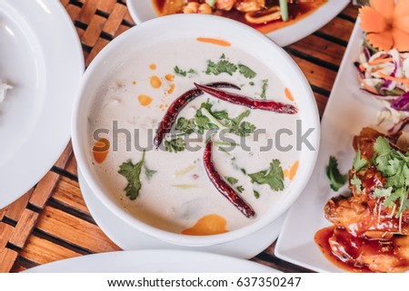 Chicken Coconut Soup (Tum Kha Kai Thai Food) onthe white blow over wooden table