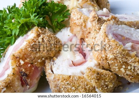 chicken cordon blue on a white plate breaded and close up