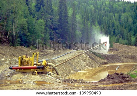 CHICKEN CREEK, ALASKA, USA - JULY 24: Gold Dredge, small mine operator wash gold off rock and sand in Chicken Creek on July 24, 1997 in Alaska, USA.