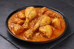 Chicken curry or masala,Kerala style chicken curry using fried coconut in traditional way and arranged in a black  ceramic vessel which is placed on a graphite sheet with grey background,isolated.