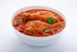 Chicken curry or masala , spicy reddish chicken leg piece dish garnished with coriander leaf and  fresh green chilli which is arranged in a white ceramic bowl with white background,isolated.