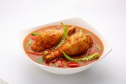 Chicken curry or masala , spicy reddish chicken leg piece dish garnished with coriander leaf and  fresh green chilli arranged in a white ceramic bowl with white background,isolated.