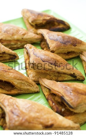 Chicken curry puff on green plate isolated white background