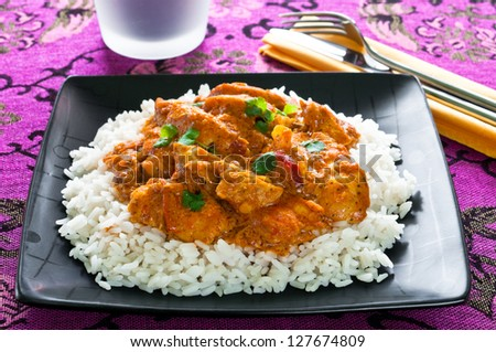 Chicken curry with rice on black plate