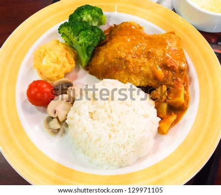 Chicken curry with rice on yellow plate