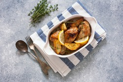 Chicken drumsticks baked with potatoes , lemon and herbs in white ceramic pan. Top view