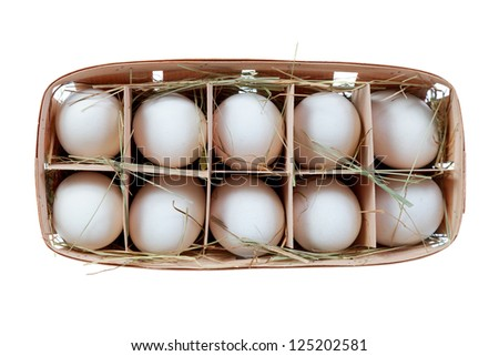 Chicken egg in a basket with straw isolated on a white background - stock photo