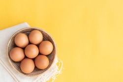 Chicken eggs, brown eggs, broken egg in carton box on yellow background. Top view natural eggs in carton box product concept.
