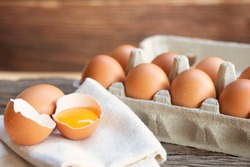 Chicken eggs, brown eggs, broken egg with yolk on calico at wooden rustic table. Natural eggs product concept.