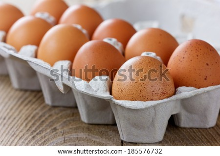 Chicken eggs in a carton box on a wooden rustic table
