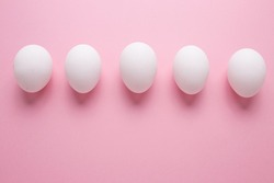 Chicken eggs in white color close-up on a pink background. A row of eggs.