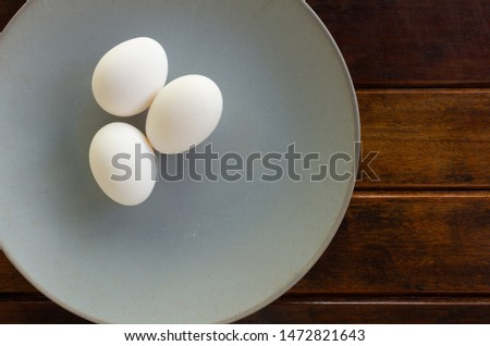 Chicken eggs on a plate and a wooden table. Copy Space Organic and natural food. Vegetarian food.