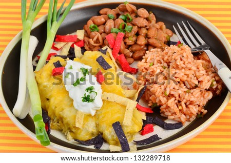 Chicken enchiladas in cheese sauce on Mexican Dinner plate with Spanish Rice and Borracho Beans against colorful orange and yellow background.