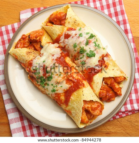 Chicken enchiladas with spicy tomato sauce and melted cheese.